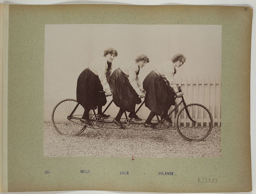 Old picture of three women on a bike in matching skirt uniforms. I guess this was a sport...