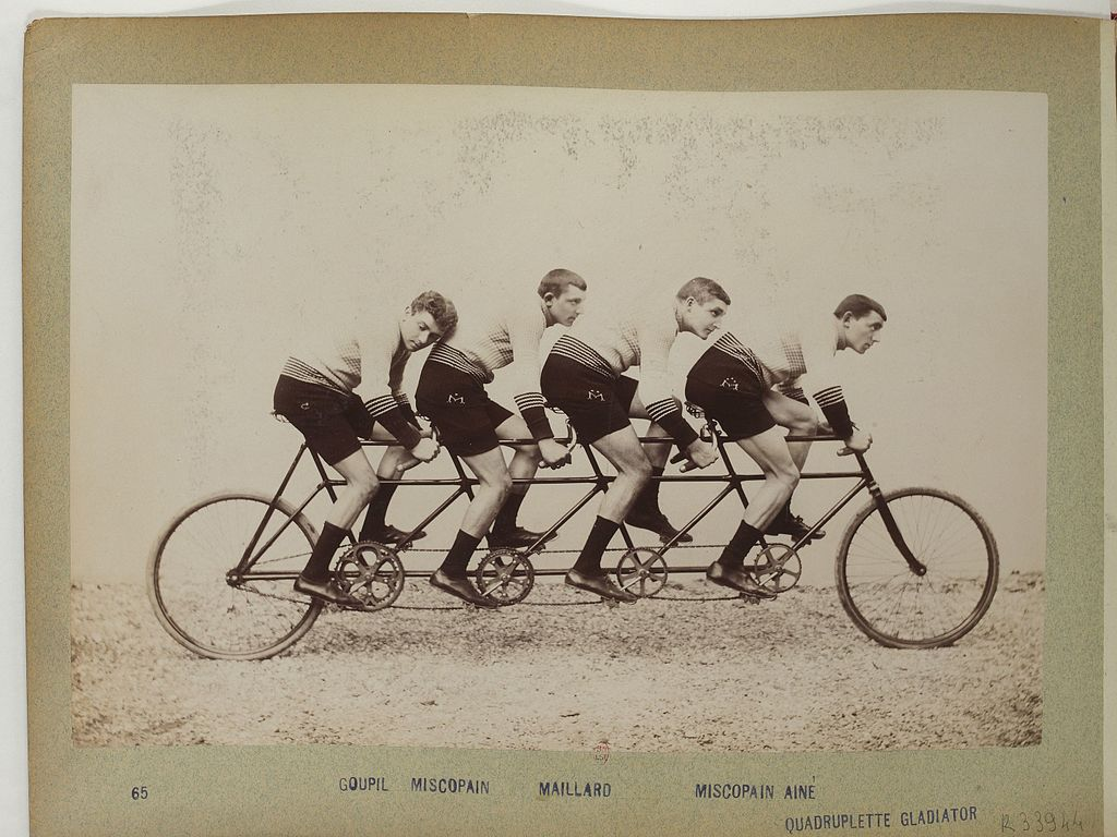 Old timey picture of four gentleman athletes on a bicycle built for four.