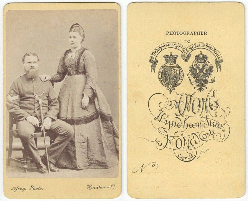 Beardy brit soldier and his wife, presumably, on an old card-style photograph.
