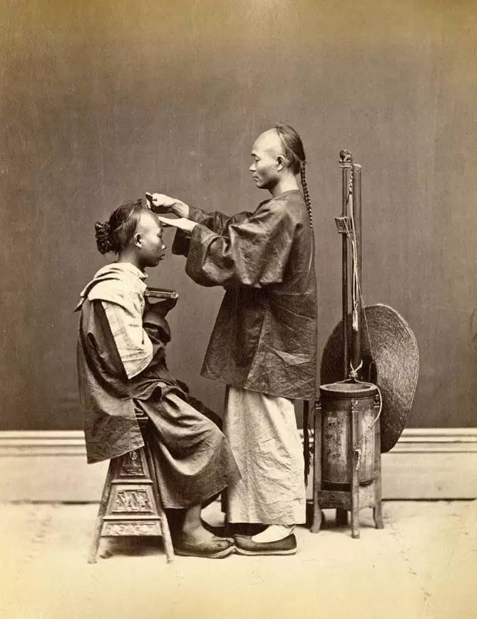 A barber (or photographer's assistant playing a barber) in the studio with props, shaving another man's head.