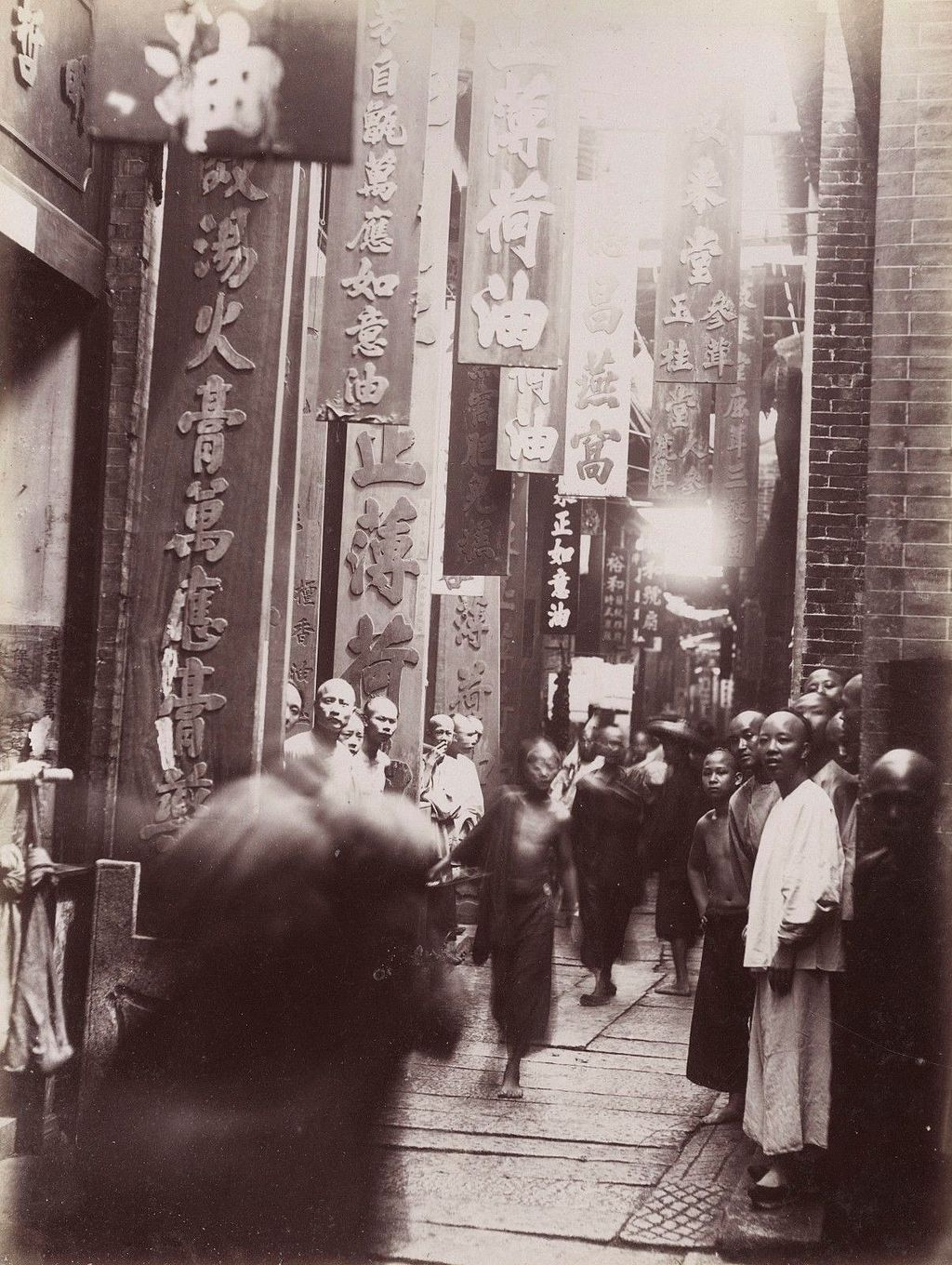 A deep, narrow street lined with tall signs, and people walking in the road.