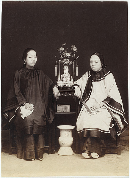 Two ladies sit for a portrait. One of them has bound feet, and the other doesn't.