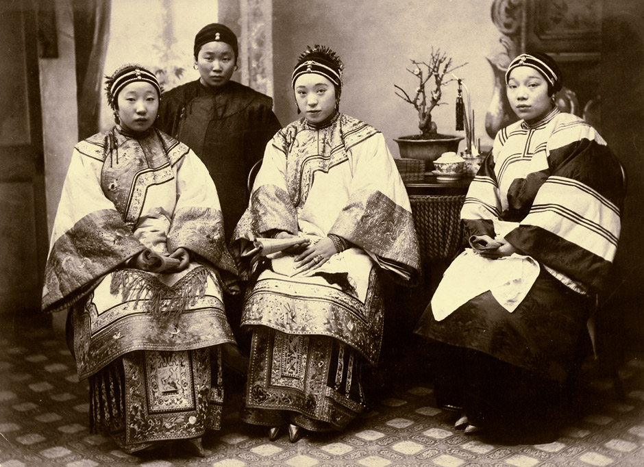 Four women, one of them probably a maid or other attendant, sitting for a photo, all holding books.