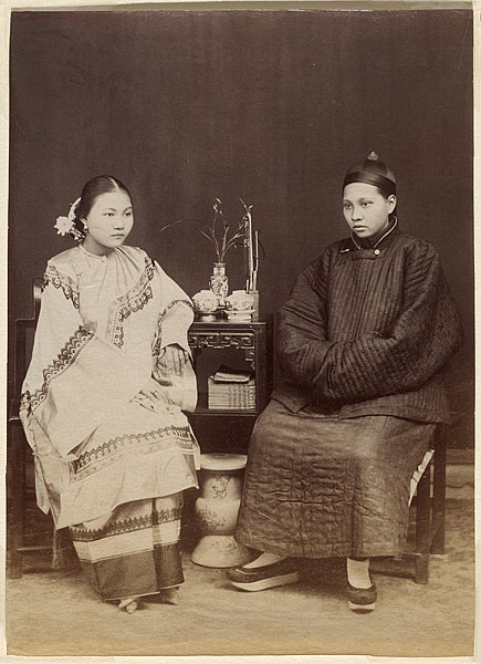 two more women sitting for a portrait at that book table. One of them is dressed as a man.