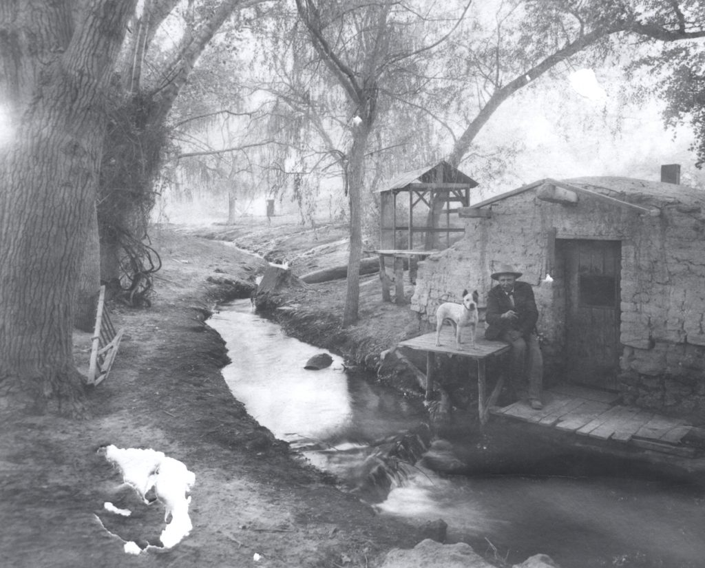 a shack by a creek, with a man and a dog sitting outside