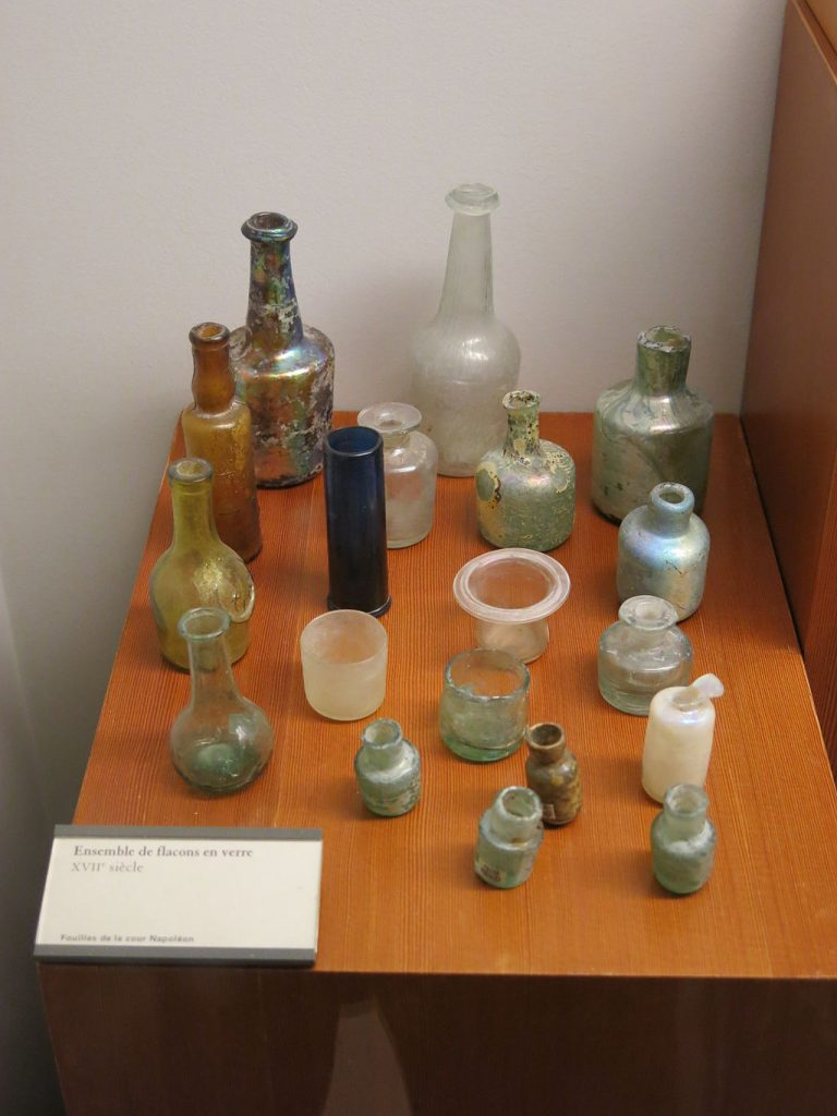 A display of ancient glass bottles of various murky clear shades