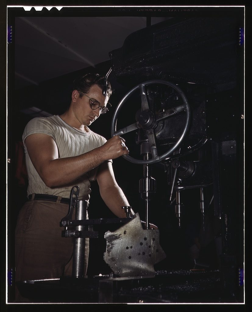 Guy in wrap around glasses and a ribbed t-shirt at a drill press.