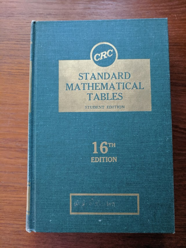 A big blue and gold old book, stuffed with tables for use with your slide rule.