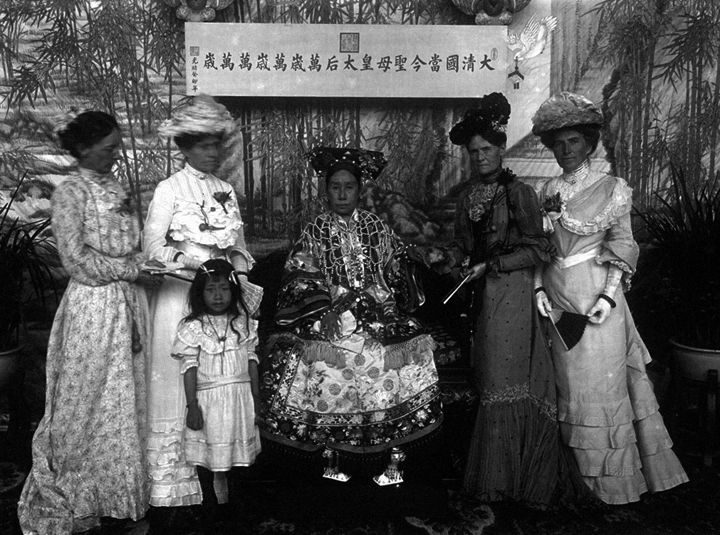 Dowager Empress Cixi and four Western ladies and a small girl in a frilly dress.