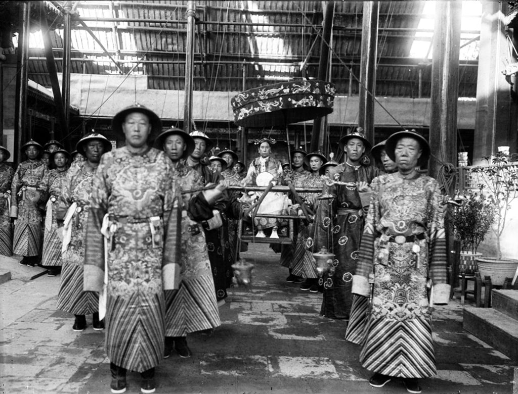 The Dowager Empress Cixi in a sedan chair with attendant court eunuchs.