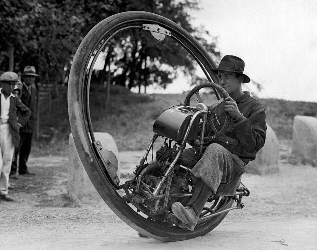 Smug man in a hat on a monowheel, which is a motorcycle that has only one wheel, but instead of the engine and driver sitting over the wheel, they sit INSIDE a really large single wheel.