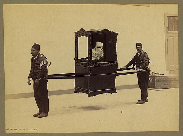 Lady in a sedan chair, with two porters lifting the chair.