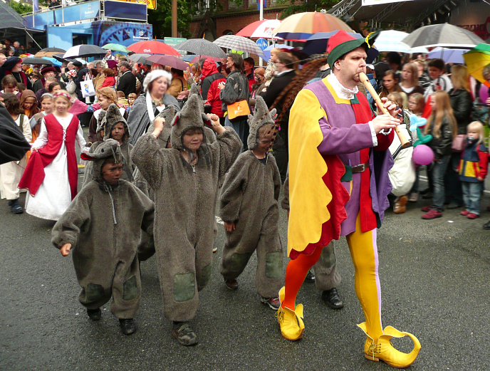 A street fair in Hamelin, Germany, with a bunch of kids dressed up as rats, and a pied piper guy.