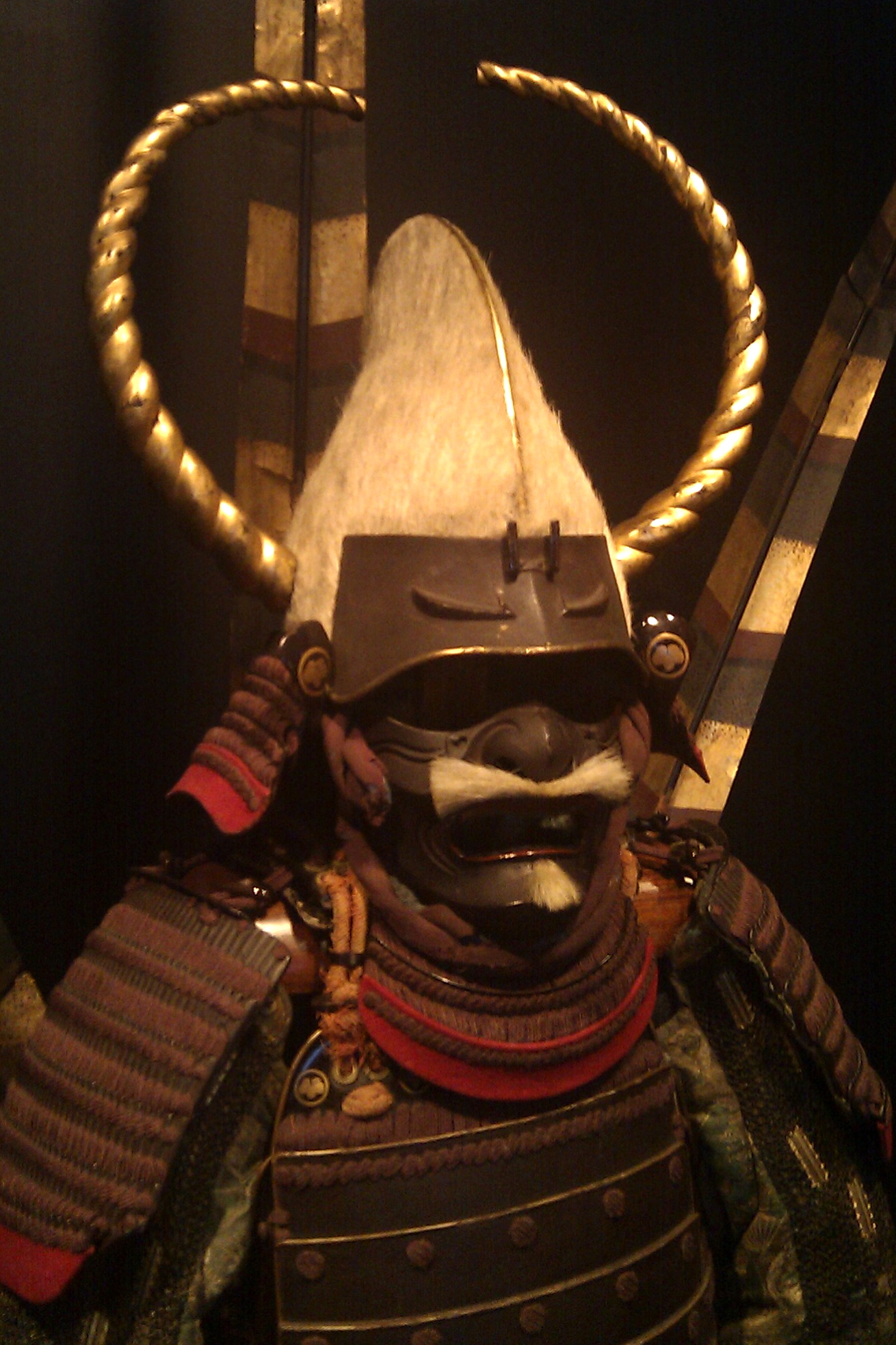 Closeup of the helmet and faceguard of a suit of Japanese armor.