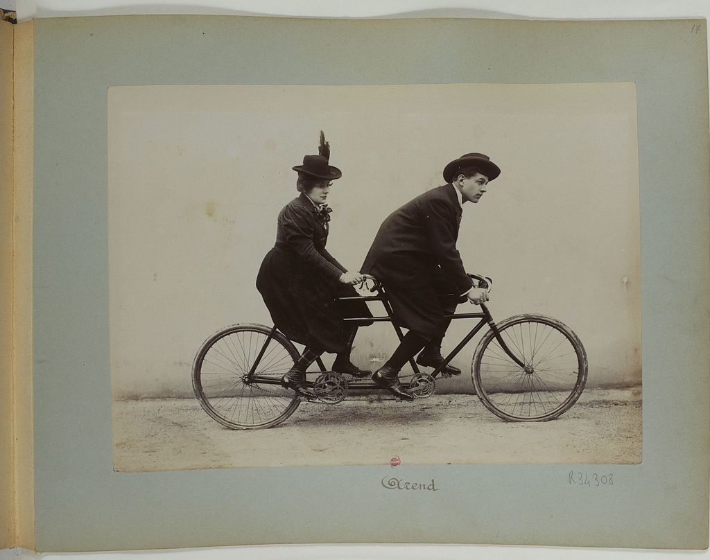 A tandem bicycle with a lady and a gent on it. Actual old photo.