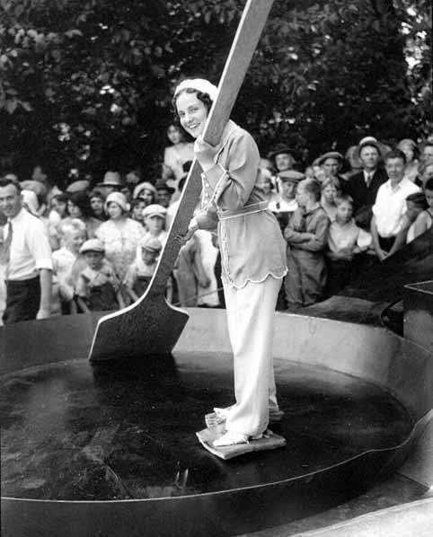 Vintage photo of a woman wearing bacon slabs on her feet, standing in a giant skillet.