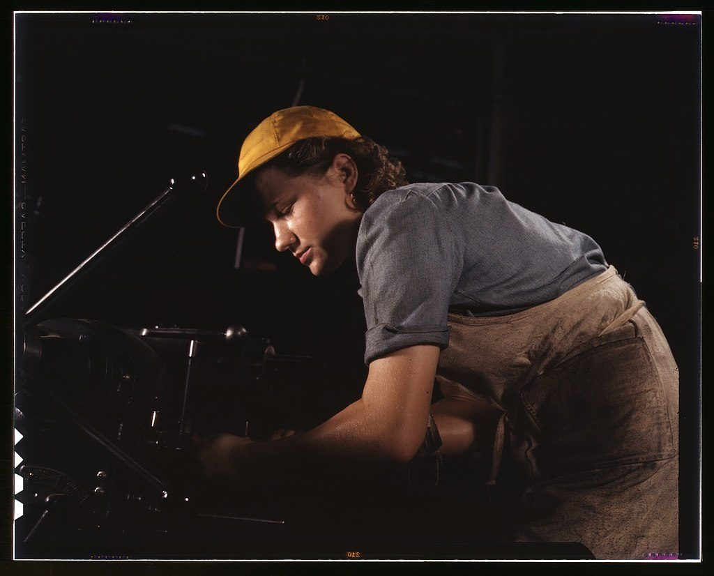 Woman in a yellow baseball cap, with short sleeves and overalls, 1944.