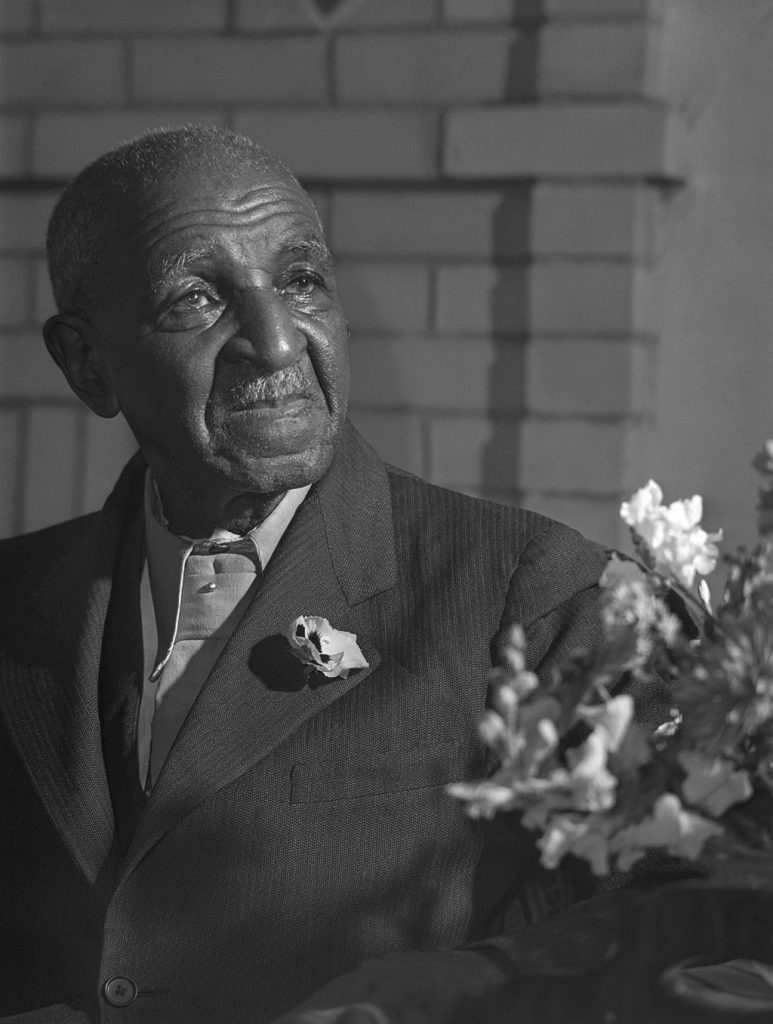 George Washington Carver with a flower arrangement of sweet pea.